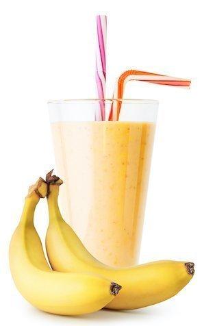Banana smoothie or yogurt in glass with bananas