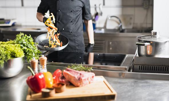 cook-tossing-vegetables-frying-pan